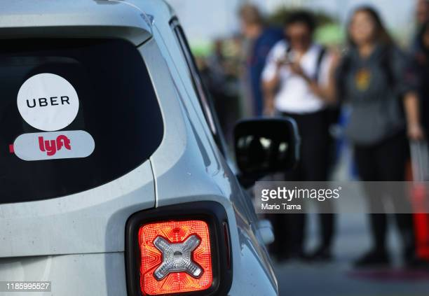 Arriving passengers wait to board Uber vehicles at the new 'LAX-it' ride-hail passenger pickup lot at Los Angeles International Airport on November...