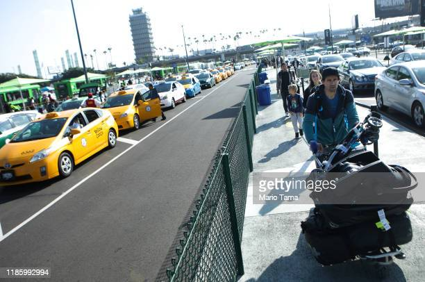 Arriving passengers walk to board Uber vehicles as taxis are lined up to pickup passengers in a separate lane at the new 'LAXit' ridehail passenger...