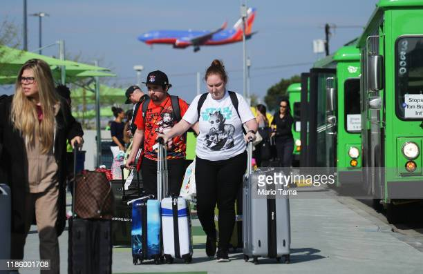 Arriving passengers walk with their luggage as they prepare to board vehicles at the new 'LAXit' ridehail passenger pickup lot at Los Angeles...