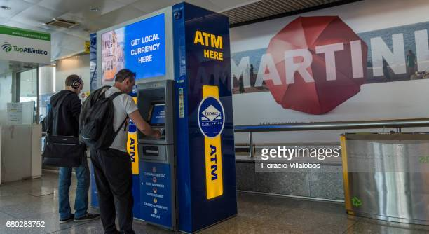 Arriving travelers use an Euronext ATM to get euros in the arrivals hall of Humberto Delgado International Airport on May 07 2017 in Lisbon Portugal...