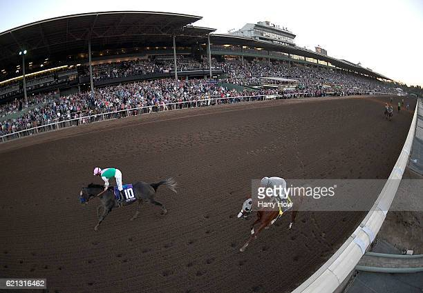 Arrogate ridden by jockey Mike Smith races to the finish line past California Chrome ridden by jockey Victor Espinoza during the Breeders' Cup...