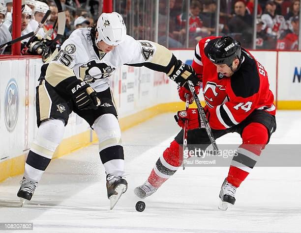 Arron Asham of the Pittsburgh Penguins battles for the puck with Tim Sestito of the New Jersey Devils in the third period of an NHL hockey game at...