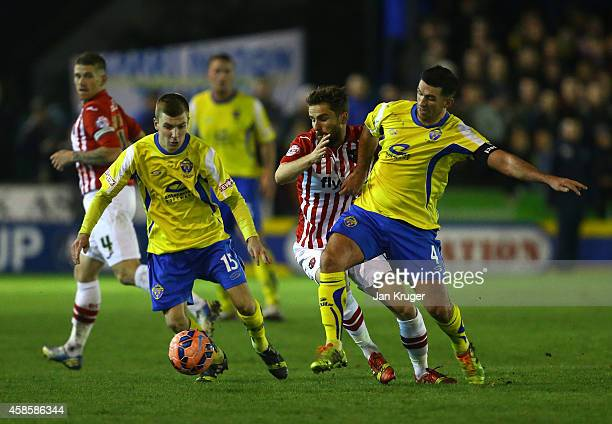 Arron Davies of Exeter City battles with David Mannix and Phil Davies of Warrington Town during the FA Cup First Round match between Warrington Town...