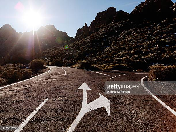 arrow indicating side road in mountain landscape - fork stock pictures, royalty-free photos & images