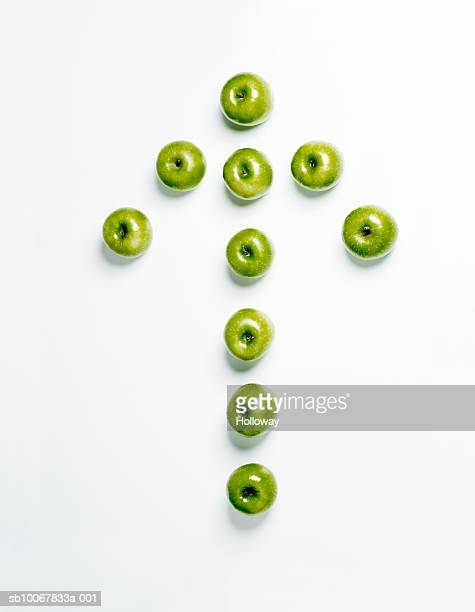 Arrow made from green apples on white background