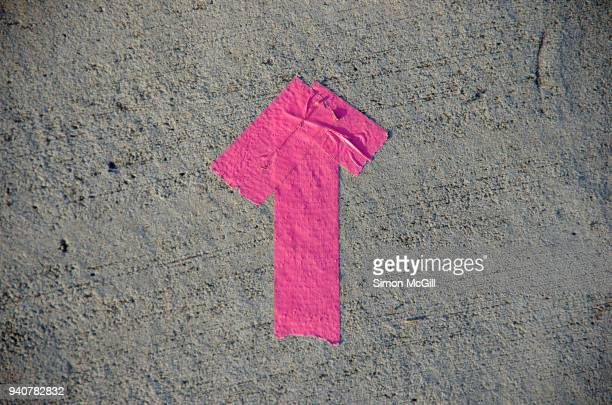 Arrow made from pink duct tape on a concrete footpath