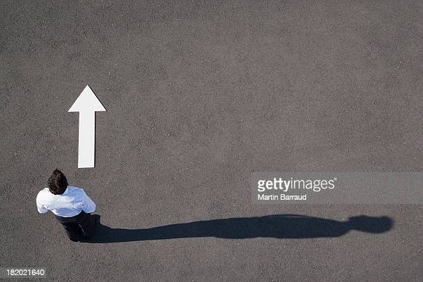 arrow on pavement pointing away from businessman - thoroughfare stock photos and pictures