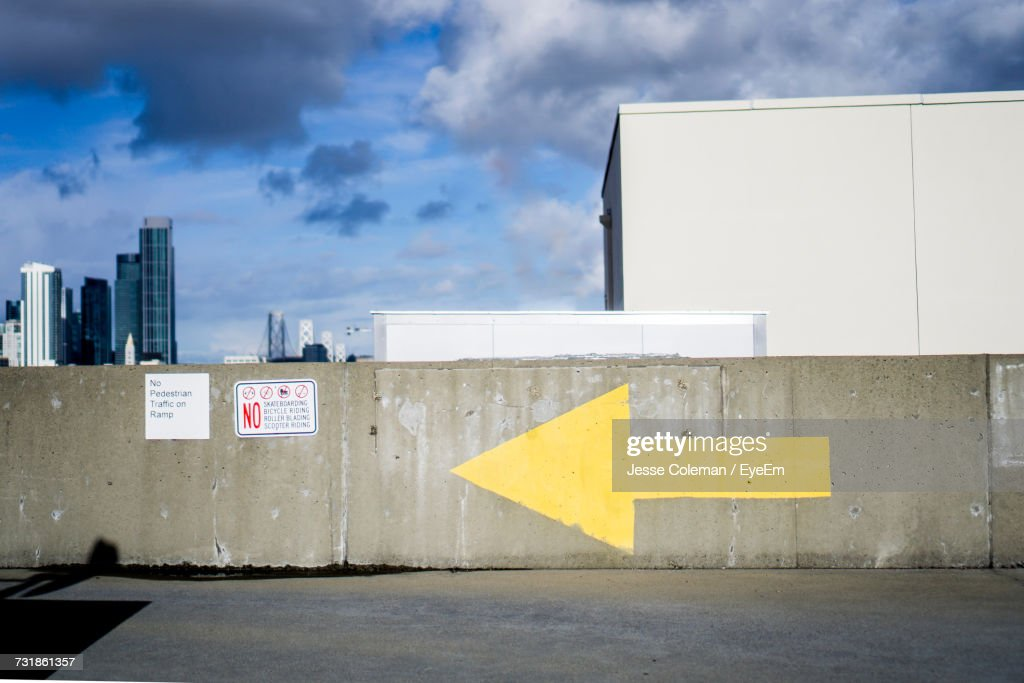 Arrow On Wall Against Sky : Stock Photo