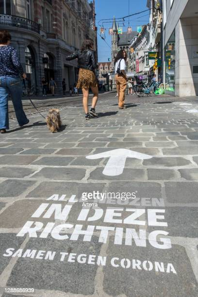 Arrow painted on pavement to indicate walking direction for shoppers in shopping street during 2020 COVID-19 / coronavirus pandemic, Ghent, Belgium.