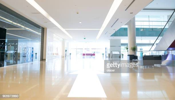 arrow pointing into empty shopping center in sunset, dubai - shopping centre stock photos and pictures