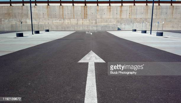 arrow road marking on asphalt - vanishing point stock pictures, royalty-free photos & images