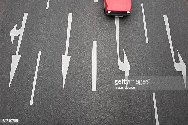 Arrow signs on a road and a car