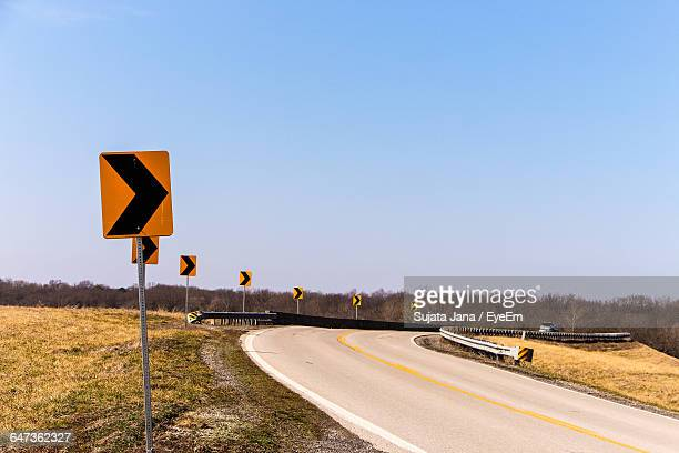 arrow signs on field by empty road against clear sky - curved arrows stock-fotos und bilder
