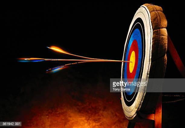 arrow splitting another arrow in bull's-eye of target - arco y flecha fotografías e imágenes de stock