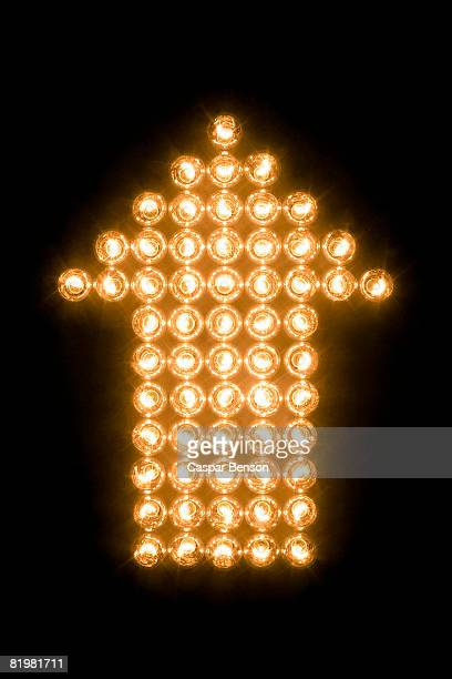 arrow symbol made with illuminated light bulbs - arrow sign stock photos and pictures