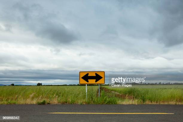 arrow symbol on empty road by field against cloudy sky - detour sign stock photos and pictures