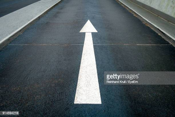 arrow symbol on road - guidance stock pictures, royalty-free photos & images
