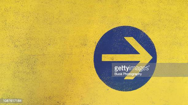 arrow symbol painted on asphalt in parking garage - yellow stock pictures, royalty-free photos & images