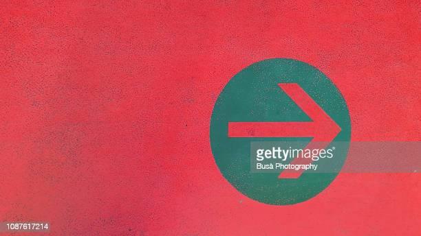 Arrow symbol painted on asphalt in parking garage