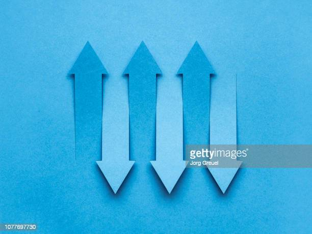 arrows cut out from a sheet of paper - toned image stock pictures, royalty-free photos & images