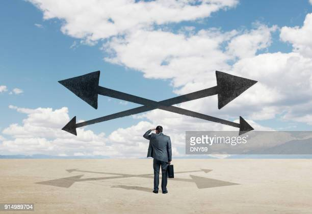 arrows point in all directions as businessman looks for guidance - morality stock photos and pictures