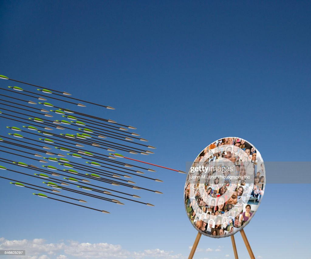 Arrows shooting towards target with faces in blue sky : Stock Photo