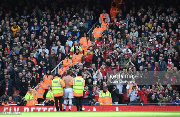 Arsenal and Bournemouth fans applaud a pitch invader during the Premier League match between Arsenal FC and AFC Bournemouth at Emirates Stadium on...