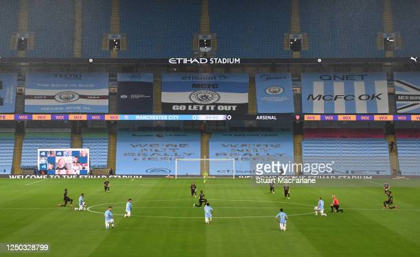 Arsenal and Man City players 'take a knee' before the Premier League match between Manchester City and Arsenal FC at Etihad Stadium on June 17 2020...