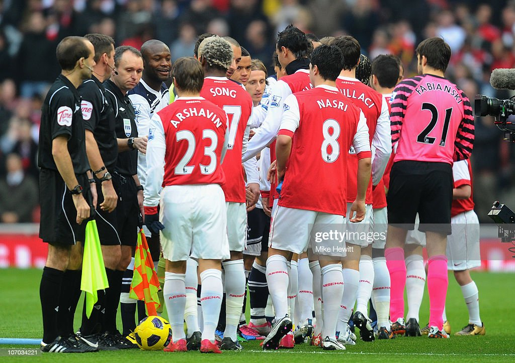 Arsenal and Tottenham players shake hands before the Barclays Premier League match between Arsenal and Tottenham Hotspur at the Emirates Stadium on November 20, 2010 in London, England.