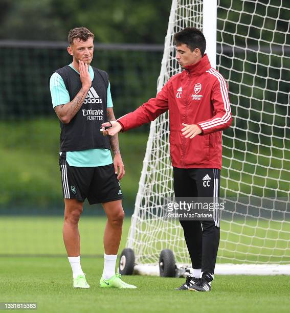 Arsenal assistant coach Carlos Cuesta talks to Ben White during a training session at London Colney on July 30, 2021 in St Albans, England.