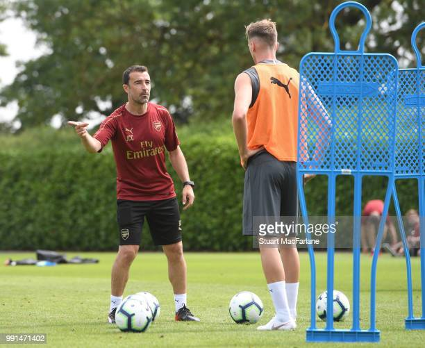 Arsenal assistant coach Juan Carlos Carcedo talks to Rob Holding during a training session at London Colney on July 4 2018 in St Albans England