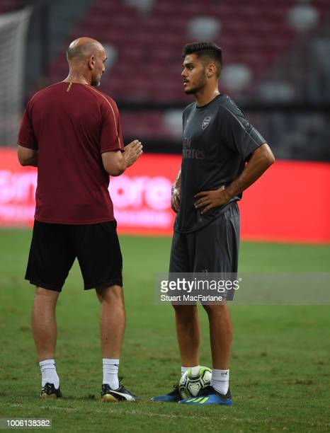 Arsenal assistant coach Steve Bould talks to Konstantinos Mavropanos during a training session at the Singapore National Stadium on July 27 2018 in...