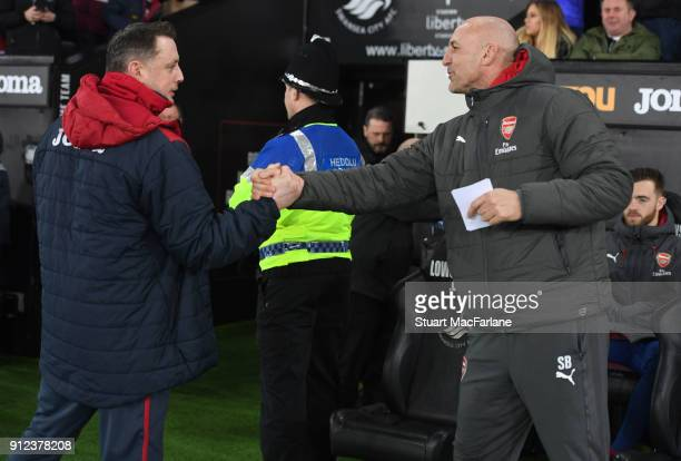 Arsenal assistant manager Steve Bould shakes hands with Swansea goalkeeping coach Tony Roberts before the Premier League match between Swansea City...