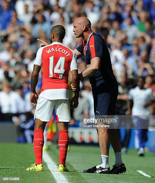 Arsenal assistant manager Steve Bould talks to striker Theo Walcott during the Barclays Premier League match between Chelsea and Arsenal on September...