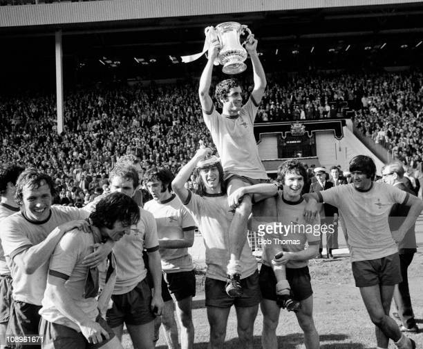 Arsenal captain Frank McLintock celebrates with the trophy while on the shoulders of teammates Charlie George and Pat Rice after the Arsenal v...