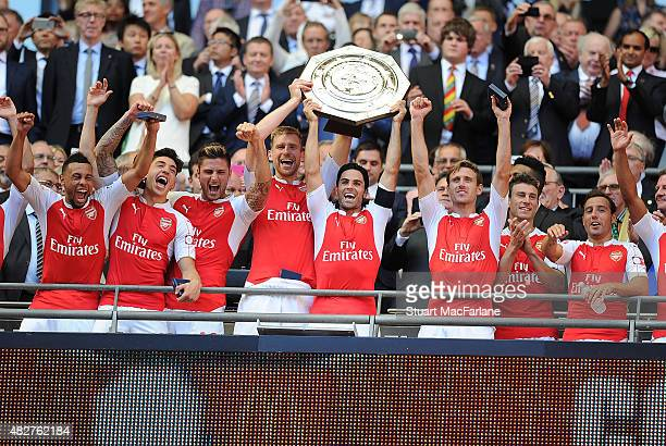 Arsenal captain Mikel Arteta lifts the Community Shield with vice captain Per Mertesacker after the FA Community Shield match between Chelsea and...