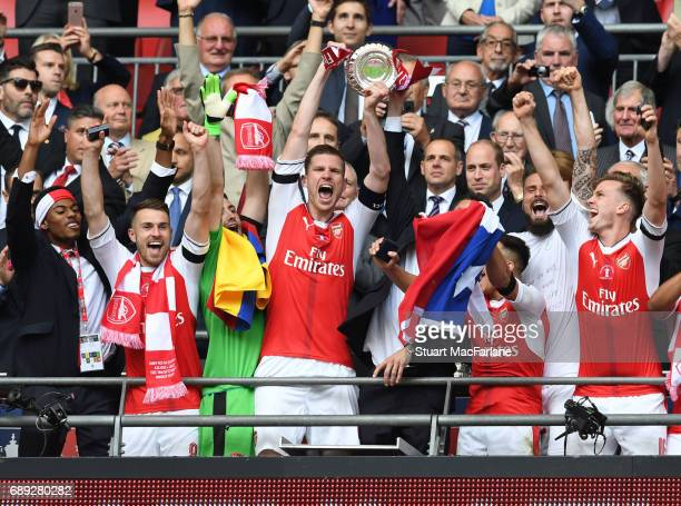 Arsenal captain Per Mertesacker lifts the FA Cup with Jeff ReineAdelaide Aaron Ramsey Rob Holding and Alexis Sanchez after the Emirates FA Cup Final...