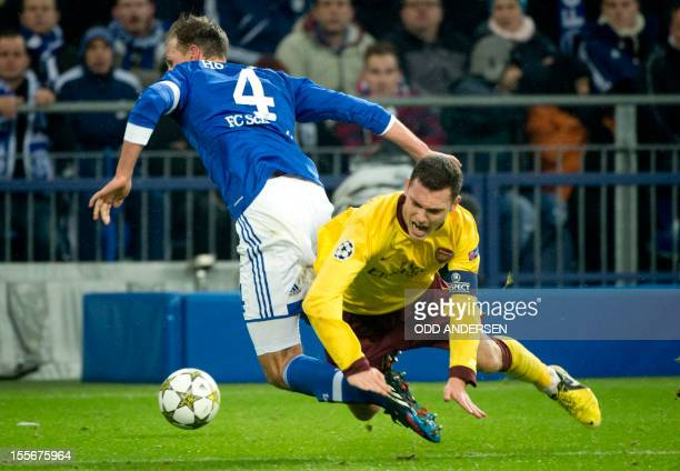 Arsenal captain Thomas Vermaelen and Schalke's defender Benedikt Hoewedes vie for the ball during the UEFA Champions league group B football match...