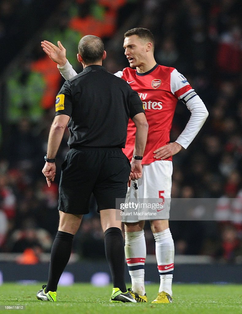 Arsenal captain Thomas Vermaelen talks to referee Mike Dean during the Barclays Premier League match between Arsenal and Manchester City at Emirates Stadium on January 13, 2013 in London, England.