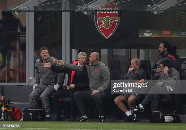 Arsenal coach Arsene Wenger exchanges words with assistant coach Steve Bould during the UEFA Europa League Round of 16 match between AC Milan and...