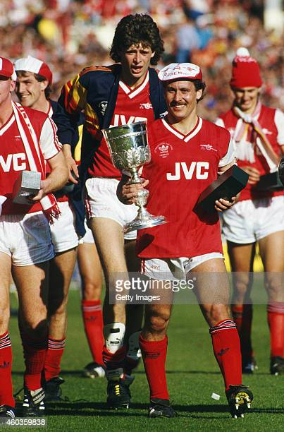 Arsenal defender and captain Kenny Sansom holds the trophy whilst Niall Quinn celebrates behind after the 1987 Littlewoods Cup Final victory against...