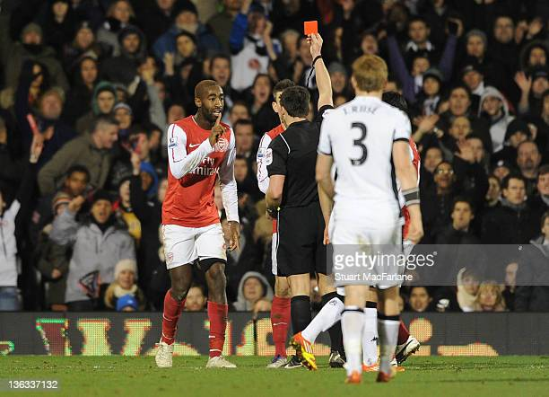 Arsenal defender Johan Djourou is shown the red card by referee Lee Probert during the Barclays Premier League match between Fulham and Arsenal at...