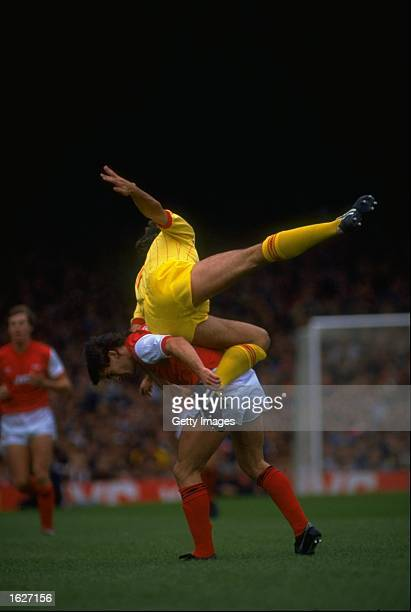 Arsenal defender Kenny Sansom gives a lift to a Liverpool forward during the Division One match between Arsenal and Liverpool at Highbury in London....