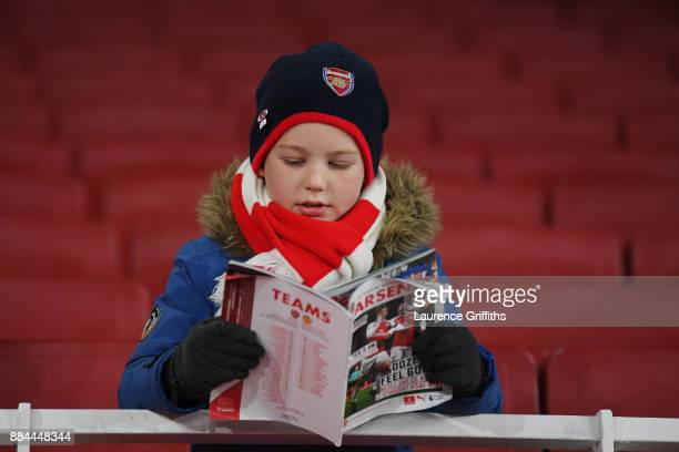 Arsenal fan reads the match day programme prior to the Premier League match between Arsenal and Manchester United at Emirates Stadium on December 2...