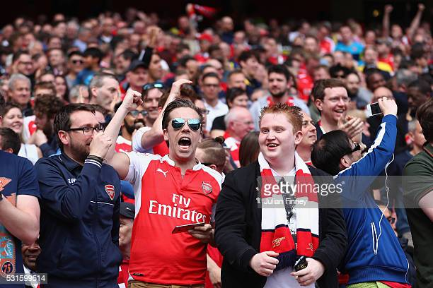Arsenal fans celebrate after hearing the Newcastle score against Tottenham Hotspur during the Barclays Premier League match between Arsenal and Aston...