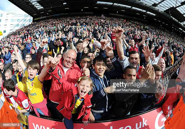 Arsenal fans celebrate after the Barclays Premier League match between Norwich City and Arsenal at Carrow Road on May 11 2014 in Norwich England