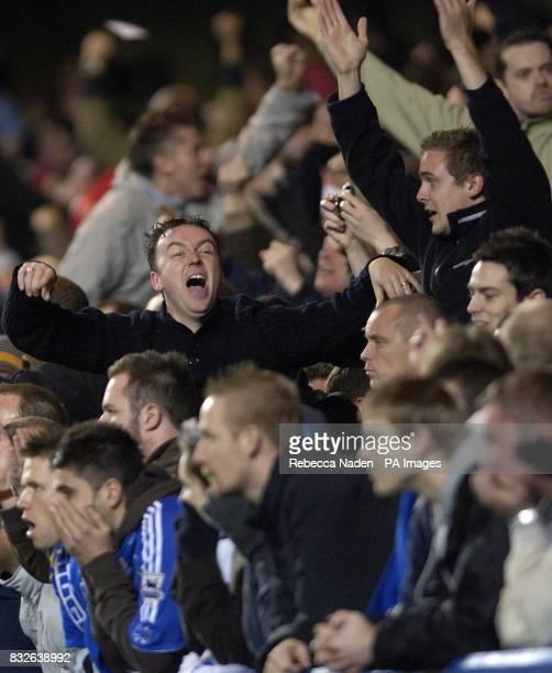 Arsenal fans celebrate Mathieu Flamini's goal as Chelsea fans look on dejected
