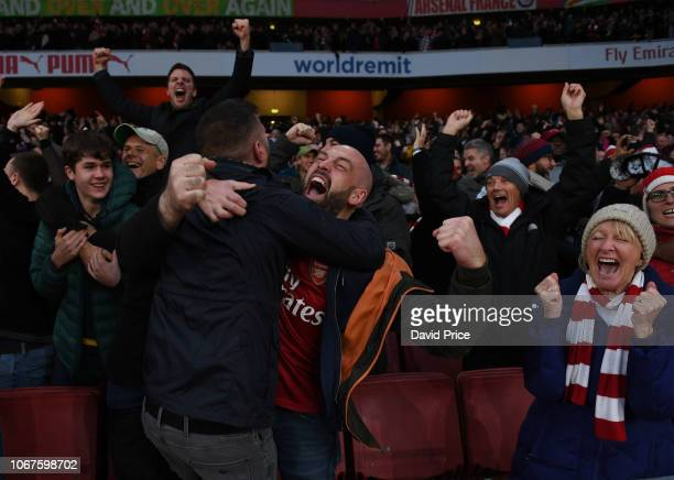 Arsenal fans celebrate the 4th goal during the Premier League match between Arsenal FC and Tottenham Hotspur at Emirates Stadium on December 2 2018...