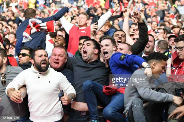 TOPSHOT Arsenal fans celebrate their team's second goal during the FA Cup semifinal football match between Arsenal and Manchester City at Wembley...