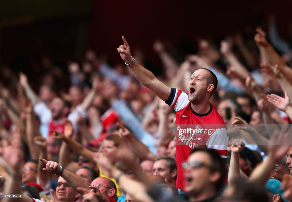 Arsenal fans celebrate victory after the Barclays Premier League match between Arsenal and Tottenham Hotspur at Emirates Stadium on September 01, 2013 in London, England.